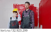 A little boy and his father painting walls - a boy puts on a helmet and holding a roller. Стоковое видео, видеограф Константин Шишкин / Фотобанк Лори