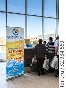 The Biblio Globus travel company reception is in Larnaca International airport. Cyprus. Arrived Russian people check-in for get transfer to hotel (2013 год). Редакционное фото, фотограф Кекяляйнен Андрей / Фотобанк Лори