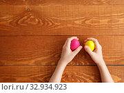 Купить «Painted Easter Egg In Hands Wooden Background», фото № 32934923, снято 25 марта 2019 г. (c) Иван Карпов / Фотобанк Лори