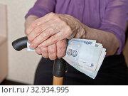 Деньги в руке пожилой женщины с тростью. Пенсия и инвалидность. Стоковое фото, фотограф Элина Гаревская / Фотобанк Лори