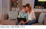 Купить «mother and son with tablet pc having video call», видеоролик № 32935111, снято 23 декабря 2019 г. (c) Syda Productions / Фотобанк Лори