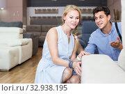 Купить «attentive man and woman are choosing sofa in store», фото № 32938195, снято 19 июня 2017 г. (c) Яков Филимонов / Фотобанк Лори