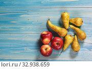 Спелые груши английского сорта Conference и три красных яблока лежат на фактурном синем столе. Стоковое фото, фотограф Наталья Гармашева / Фотобанк Лори