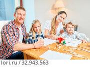 Familie und Kinder malen zusammen ihr Wunsch Traumhaus als Eigenheim. Стоковое фото, фотограф Zoonar.com/Robert Kneschke / age Fotostock / Фотобанк Лори