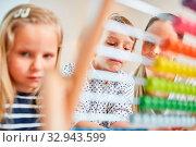 Zwei Kinder als Schüler lernen Rechnen mit dem Abakus bei der Nachhilfe. Стоковое фото, фотограф Zoonar.com/Robert Kneschke / age Fotostock / Фотобанк Лори
