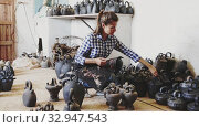 Купить «Portrait of cheerful female artisan inspecting finished production in pottery workshop», видеоролик № 32947543, снято 2 июня 2020 г. (c) Яков Филимонов / Фотобанк Лори