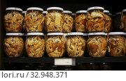 Купить «Glass jars with assorted preserved mushrooms on shelves in store», видеоролик № 32948371, снято 5 июля 2020 г. (c) Яков Филимонов / Фотобанк Лори