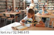 Купить «Schoolchildren preparing for lesson in school library, reading textbooks», видеоролик № 32948615, снято 24 сентября 2019 г. (c) Яков Филимонов / Фотобанк Лори