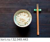 Купить «Top view of portion of boiled rice in bowl and chopsticks on rest on dark wooden desk», фото № 32949443, снято 25 мая 2020 г. (c) easy Fotostock / Фотобанк Лори