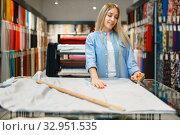 Купить «Woman measures the fabric closeup, textile store», фото № 32951535, снято 8 ноября 2019 г. (c) Tryapitsyn Sergiy / Фотобанк Лори