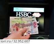 Купить «Doha, Qatar - Nov 17. 2019. Qatari rials in hand on the background of ATM of HSBC Bank», фото № 32952607, снято 17 ноября 2019 г. (c) Володина Ольга / Фотобанк Лори