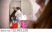 A young woman brushes her hair looking in the mirror. Стоковое видео, видеограф Константин Шишкин / Фотобанк Лори