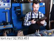 Young man worker working at restoring boots. Стоковое фото, фотограф Яков Филимонов / Фотобанк Лори