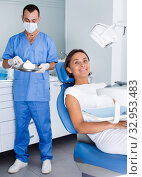 Купить «Young female is sitting satisfied after treatment in dental office», фото № 32953483, снято 10 июля 2017 г. (c) Яков Филимонов / Фотобанк Лори