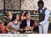 Купить «African American waiter recommending dishes from restaurant menu», фото № 32953503, снято 7 марта 2018 г. (c) Яков Филимонов / Фотобанк Лори