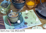 Masala tea. A Cup of traditional Indian tea masala tea with ingredients to prepare. Cinnamon, anise, sugar, black tea, pepper, cloves, turmeric on a wooden table. Стоковое фото, фотограф Мария Кошелева / Фотобанк Лори