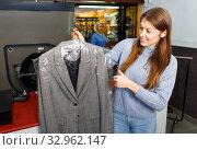 Купить «Portrait of cheerful female laundry customer holding clean clothes on hanger», фото № 32962147, снято 22 января 2019 г. (c) Яков Филимонов / Фотобанк Лори