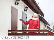 Купить «Real estate agent inviting to enter townhouse for visit. Snowall outside the building, woman stands at porch at winter season», фото № 32962459, снято 4 января 2020 г. (c) Кекяляйнен Андрей / Фотобанк Лори