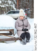 Senior woman sitting on snow covered bench at snowy table. Yellow-bellied tit is next to female, rural courtyard in village. Стоковое фото, фотограф Кекяляйнен Андрей / Фотобанк Лори