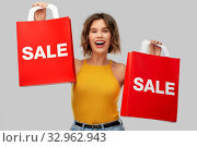 Купить «happy young woman with shopping bags on sale», фото № 32962943, снято 30 сентября 2019 г. (c) Syda Productions / Фотобанк Лори