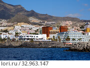 Tenerife, Spain - October 15, 2019: Waterside distant view touristic place Los Cristianos coastline, resort town, situated on south coast of Canary Islands, Spain. Редакционное фото, фотограф Alexander Tihonovs / Фотобанк Лори