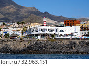 Tenerife, Spain - October 15, 2019: Waterside distant view Los Cristianos coastline, busy promenade waterfront street, touristic town, situated on south coast of Canary Islands, Spain. Редакционное фото, фотограф Alexander Tihonovs / Фотобанк Лори