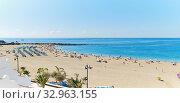 Tenerife, Spain - October 13, 2019: Panoramic view of crowd of people sunbathing on sandy beach of Playa de los Cristianos, enjoy warm weather, Tenerife, Canary Islands, Spain. Редакционное фото, фотограф Alexander Tihonovs / Фотобанк Лори