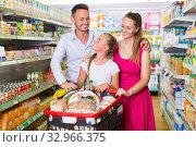 Three customers smiling with purchases in shopping cart. Стоковое фото, фотограф Яков Филимонов / Фотобанк Лори