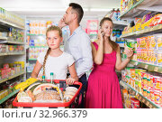 Купить «Sadly little girl customer with two adult with telephones», фото № 32966379, снято 11 июля 2017 г. (c) Яков Филимонов / Фотобанк Лори