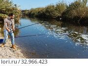 Купить «Adult man standing near river and pulling fish expressing emotions of dedication», фото № 32966423, снято 15 марта 2019 г. (c) Яков Филимонов / Фотобанк Лори