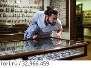 Купить «Attentive adult man exploring artworks in glass case in museum», фото № 32966459, снято 7 апреля 2019 г. (c) Яков Филимонов / Фотобанк Лори