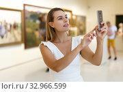 Купить «Woman photographing painting in museum», фото № 32966599, снято 28 июля 2018 г. (c) Яков Филимонов / Фотобанк Лори