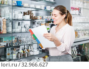 Купить «Smiling female buyer holding catalogue, choosing new tableware», фото № 32966627, снято 2 мая 2018 г. (c) Яков Филимонов / Фотобанк Лори
