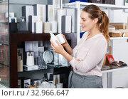 Young woman take a choise bottle for liquid soap in supermarket. Стоковое фото, фотограф Яков Филимонов / Фотобанк Лори