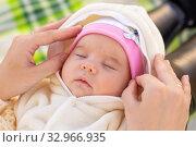 Купить «Mom fixes the cap of a two-month-old baby», фото № 32966935, снято 12 ноября 2019 г. (c) Иванов Алексей / Фотобанк Лори