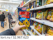 Купить «Russia Samara December 2019: A hand holds a package with chips on the background of a rack with chips in a supermarket.», фото № 32967623, снято 25 декабря 2019 г. (c) Акиньшин Владимир / Фотобанк Лори