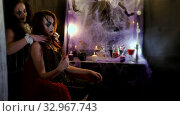 Girl with makeup for Halloween is sitting in front of a mirror. The artist throws back a lock of hair from her face. A clown comes up behind her, smiling, and puts his hands on the girl's neck. Brides of the devil laugh terribly. Стоковое видео, видеограф Константин Мерцалов / Фотобанк Лори