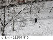 Купить «Одинокий черный пешеход идет по заснеженному тротуару вокруг дома. Город, зима, снегопад. Вид сверху», фото № 32967815, снято 22 января 2020 г. (c) Наталья Николаева / Фотобанк Лори