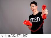 Купить «Studio shot of young handsome nerd man wearing eyeglasses holding old telephone against gray background», фото № 32971167, снято 26 января 2020 г. (c) easy Fotostock / Фотобанк Лори