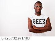 Купить «Studio shot of young happy black African nerd man smiling and wearing Geek shirt against white background», фото № 32971183, снято 26 января 2020 г. (c) easy Fotostock / Фотобанк Лори