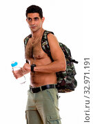 Купить «Studio shot of young muscular Persian man holding water bottle while thinking and checking time shirtless», фото № 32971191, снято 26 января 2020 г. (c) easy Fotostock / Фотобанк Лори