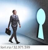 Businessman walking towards keyhole in challenge concept. Стоковое фото, фотограф Elnur / Фотобанк Лори