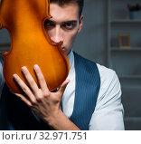 Купить «Young musician man practicing playing violin at home», фото № 32971751, снято 15 августа 2017 г. (c) Elnur / Фотобанк Лори
