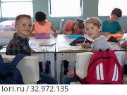 Schoolboys sitting at desks in an elementary school classroom. Стоковое фото, агентство Wavebreak Media / Фотобанк Лори