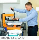 Купить «Man using a serigraph press to print a shirt in a workshop», фото № 32972419, снято 3 августа 2020 г. (c) Яков Филимонов / Фотобанк Лори