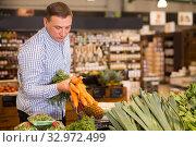 Купить «Male consumer choosing carrots in supermarket», фото № 32972499, снято 9 октября 2019 г. (c) Яков Филимонов / Фотобанк Лори
