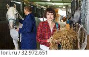 Worker spreading armfuls of hay at stable. Стоковое фото, фотограф Яков Филимонов / Фотобанк Лори