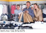 Купить «Glad couple and teenager with shopping bags», фото № 32972675, снято 13 апреля 2017 г. (c) Яков Филимонов / Фотобанк Лори