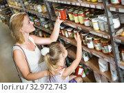 Купить «Mother with daughter shopping conserve crushed tomatoes», фото № 32972743, снято 23 февраля 2020 г. (c) Яков Филимонов / Фотобанк Лори