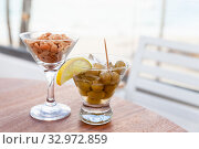 Купить «Green olives with lemon and ice and peanuts», фото № 32972859, снято 6 января 2020 г. (c) EugeneSergeev / Фотобанк Лори